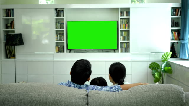 happy family watching tv with green screen monitor in living room - guardare la tv video stock e b–roll