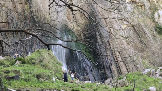 happy family waving to the camera in front of a rock wall where a waterfall drops. - parque natural stock videos and b-roll footage