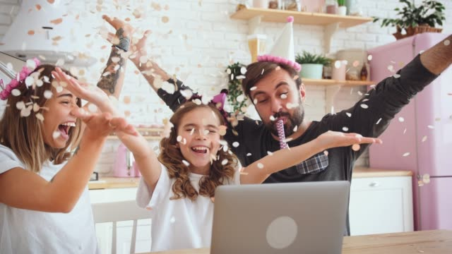 Happy family with a daughter celebrating birthday in kitchen using laptop for a video call during online birthday party. Family throwing confetti and having fun, slow motion