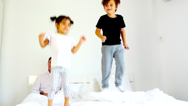 happy family with children playful in the bedroom at home - bed furniture stock videos & royalty-free footage