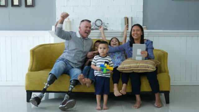glückliche familie mit behinderten menschen vor dem fernseher zusammen - personen mit behinderung stock-videos und b-roll-filmmaterial