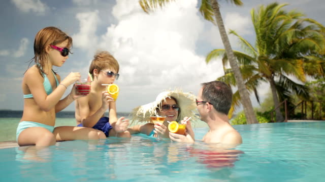 stockvideo's en b-roll-footage met happy family with kids and soft drinks - tropische drankjes