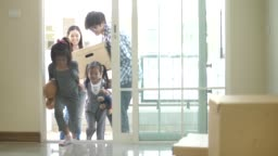 Happy family with kids holding boxes entering new modern house