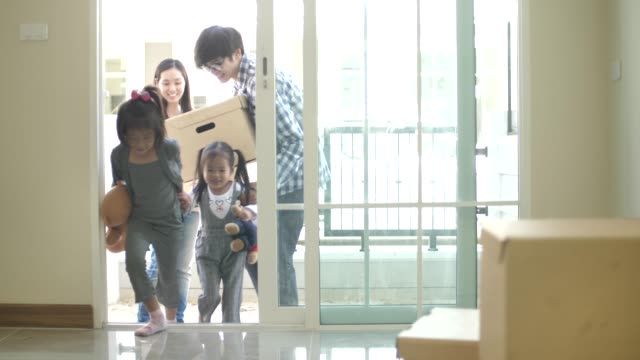 happy family with kids holding boxes entering new modern house - flat stock videos & royalty-free footage