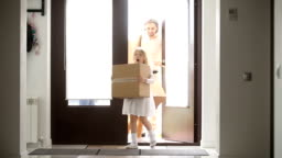 Happy family with kids holding boxes opening door entering house