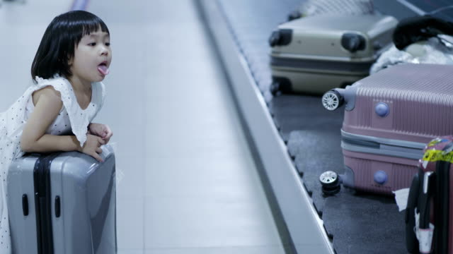 小さな女の子 (スーツケースを空港) と幸せな家庭 - マグカップ点の映像素材/bロール