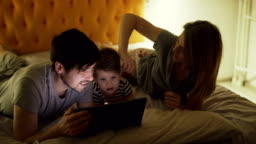 Happy family with little son lying in bed at home and surfing social media on tablet computer before sleeping