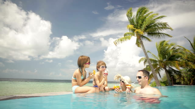happy family with soft drinks resting in pool