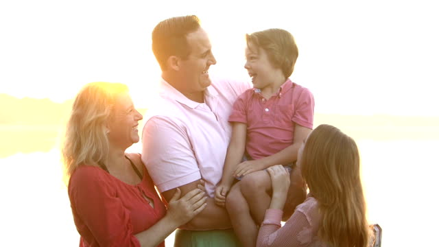 happy family with two children outdoors - adulazione video stock e b–roll