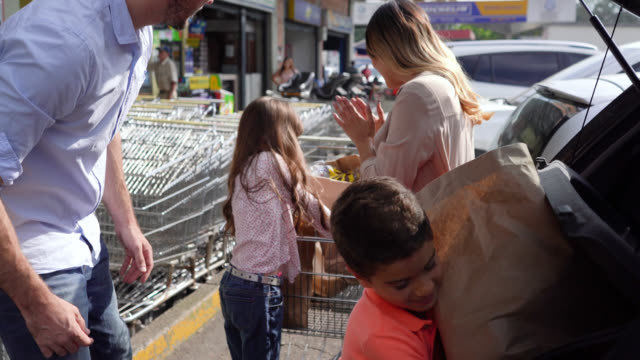 vídeos de stock e filmes b-roll de happy family working together placing shopping bags from cart to trunk outside the supermarket - arranjo