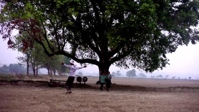 happy farmer & children during rainy season - wide shot stock videos & royalty-free footage
