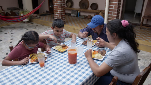 happy farmer family enjoying lunch together talking and smiling - developing countries stock videos & royalty-free footage