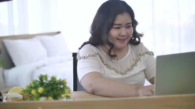 自宅でコンピュータを使用して幸せな脂肪の女性 - overweight点の映像素材/bロール