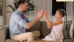 happy father and daughter playing clapping game at home