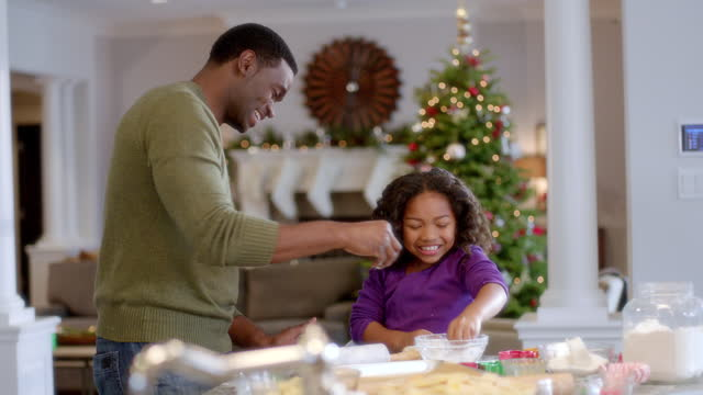 happy father and daughter sprinkle flour on cookie dough (dolly-shot) - keks stock-videos und b-roll-filmmaterial
