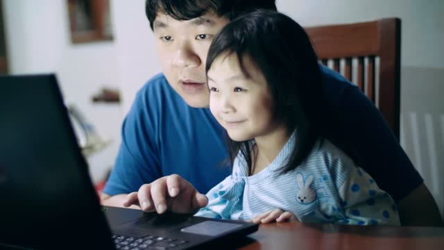 happy father and daughter using laptop while studying at home - genderblend stock videos & royalty-free footage