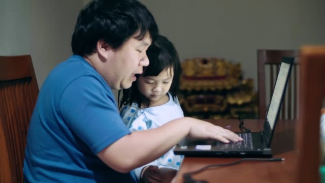 vídeos de stock e filmes b-roll de happy father and daughter using laptop while studying at home - genderblend