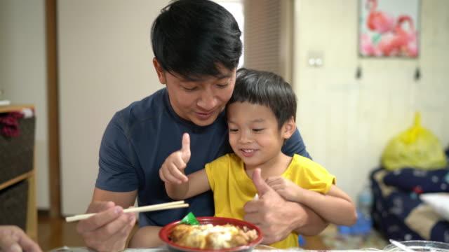 父と息子、小さな男の子がカツ丼を食べて楽しむ、家でご飯と一緒に日本の揚げ豚肉、2歳 - son点の映像素材/bロール