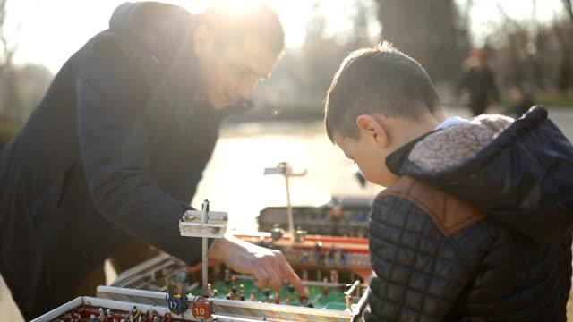 vídeos de stock, filmes e b-roll de feliz pai e filho jogando futebol de mesa no parque - competition round