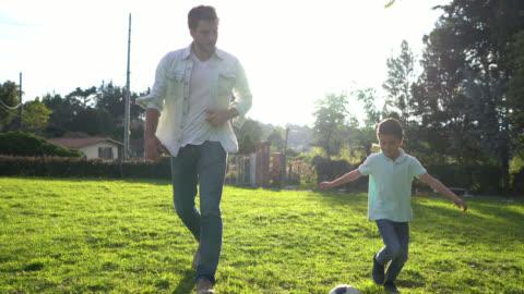 glücklicher vater und sohn spielen mit einem fußball in ihrem hinterhof - vater stock-videos und b-roll-filmmaterial