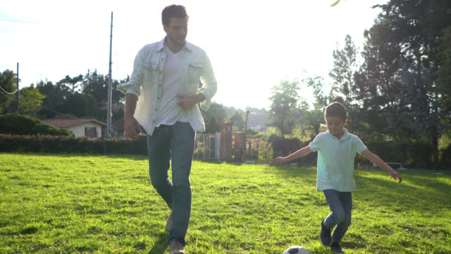 happy father and son playing with a soccer ball at their backyard - etnia latino americana video stock e b–roll