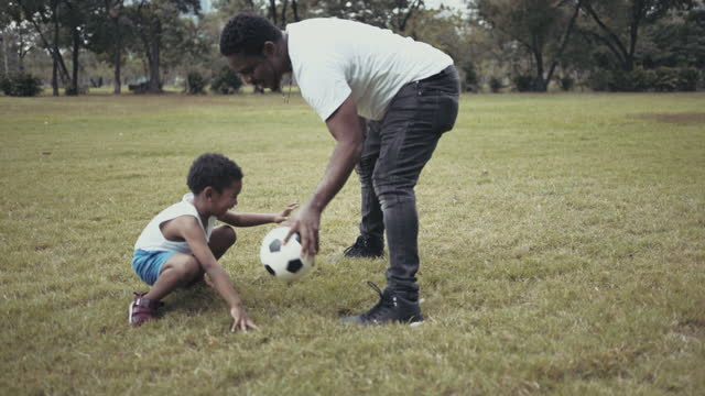vidéos et rushes de père et fils heureux jouant avec un bille de football dans le stationnement public - afro américain