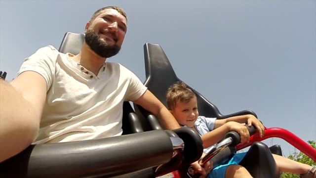 happy father and son ride on a roller coaster - amusement park ride stock videos and b-roll footage