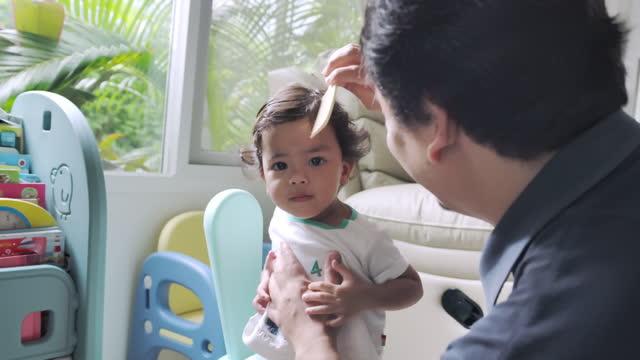 vidéos et rushes de père heureux peignant les cheveux de son fils - son