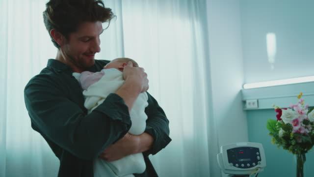 stockvideo's en b-roll-footage met gelukkige vader houdt slapende pasgeboren baby in de wijk - pasgeborene