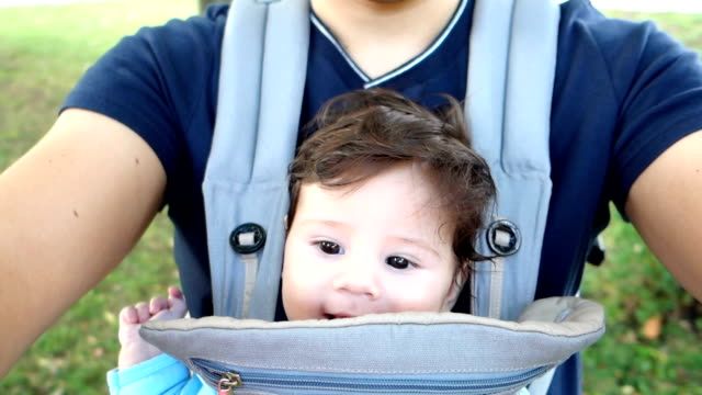 happy father holds his baby boy in a baby carrier - genderblend stock videos & royalty-free footage