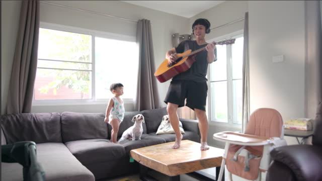 vídeos de stock, filmes e b-roll de pai feliz tocando guitarra com um filho e dois cachorros na sala de estar em casa. - animal de estimação