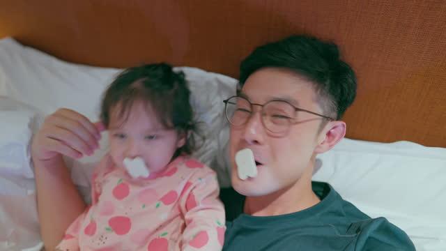 vídeos y material grabado en eventos de stock de padre feliz jugando con linda hija en la habitación del hotel - genderblend