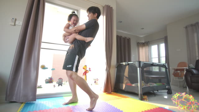 a happy father raising his baby boy and play together at home - genderblend stock videos & royalty-free footage