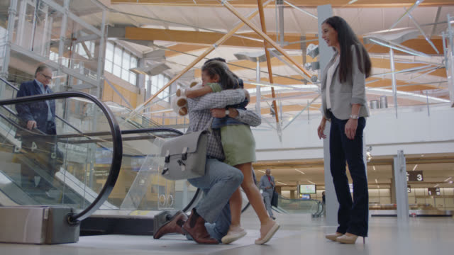happy father rushes to hug young daughter and wife at airport arrivals. - ホームカミング点の映像素材/bロール