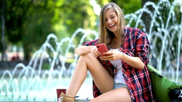 glückliche frauen surfen und sms auf dem handy - shorts stock-videos und b-roll-filmmaterial