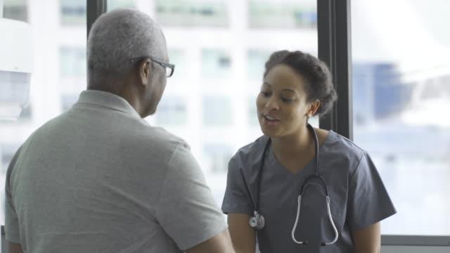 vídeos de stock, filmes e b-roll de happy female doctor embracing senior male patient in clinic - clínica médica