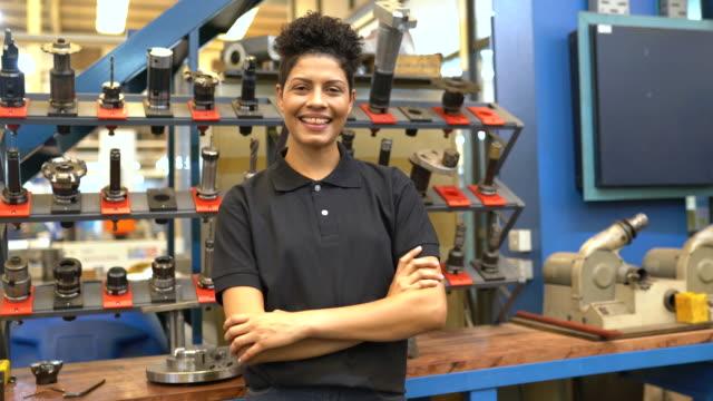 stockvideo's en b-roll-footage met gelukkige vrouwelijke ingenieur die zich in fabrieksworkshop bevindt - productielijn werker