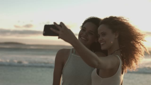 stockvideo's en b-roll-footage met happy female friends taking selfie at beach - zelfportret fotograferen