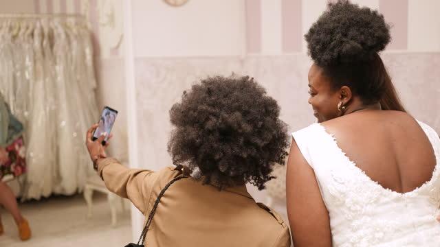 幸せな女性の友人は、ウェディングドレスショップで自分撮りを取ります - ウェディングドレス点の映像素材/bロール