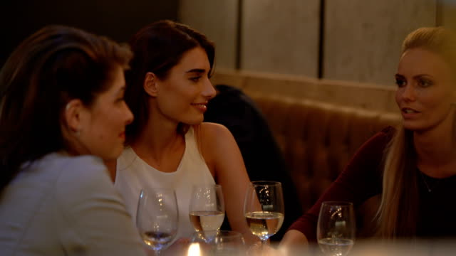 Happy Female Friends Talking In Restaurant