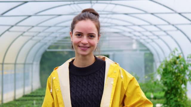 vidéos et rushes de jardinier féminin heureux dans l'imperméable restant dans la serre chaude - jardin potager