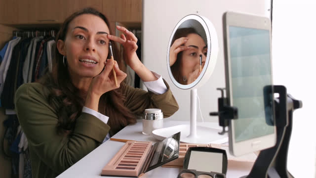 vídeos de stock e filmes b-roll de happy female influencer recording a video explaining how to do her make-up using a lighted mirror and looking very cheerful - contente