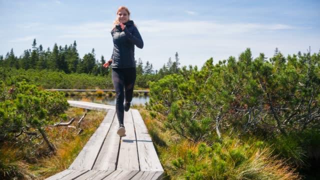 vídeos y material grabado en eventos de stock de feliz mujer corredor corriendo en la naturaleza, manteniendo un estilo de vida saludable, respirar aire fresco - mejora personal