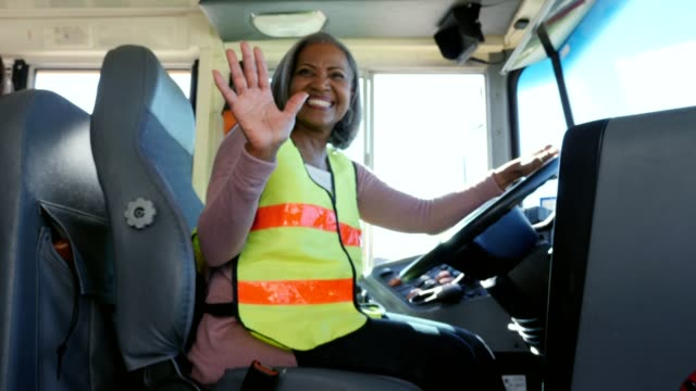 happy female school bus welcomes children onto school bus - bus driver stock videos & royalty-free footage