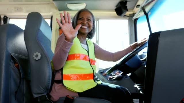 ハッピー女性スクールバスは、スクールバスに子供たちを歓迎します - 職業 運転手点の映像素材/bロール