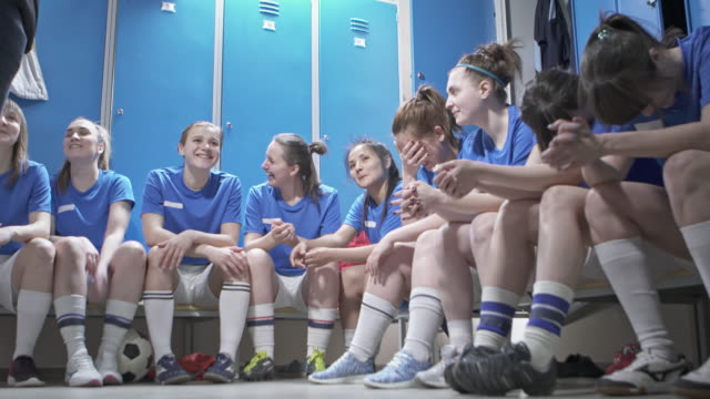 happy female soccer players talking to coach in changing room - bench stock videos & royalty-free footage