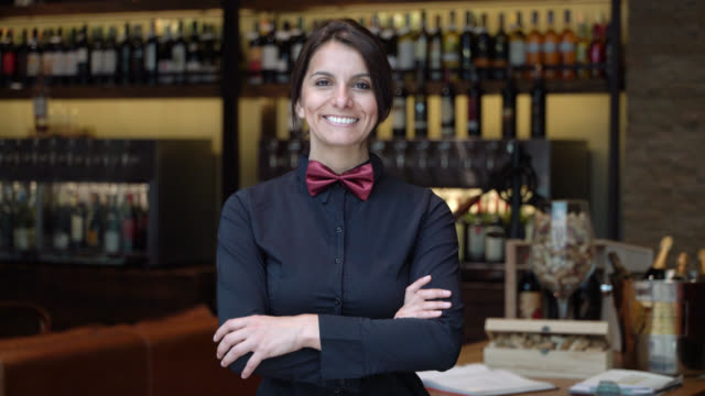 笑顔のカメラを見てワインバーで働く幸せな女性ソムリエ - ワインバー点の映像素材/bロール