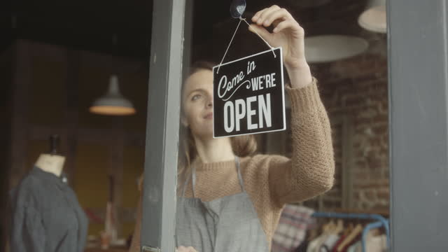 happy female store owner turning open sign on door entrance, reopening - entrance sign stock videos & royalty-free footage