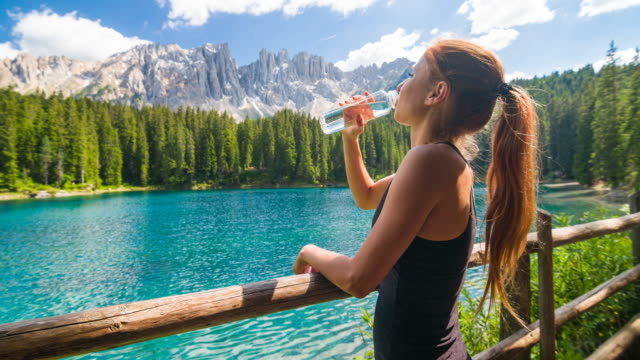 happy female tourist at mountain lake lago di carezza in dolomites enjoying breathtaking view, drinking water - cold drink stock videos and b-roll footage