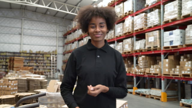 Happy female worker with arms crossed in warehouse